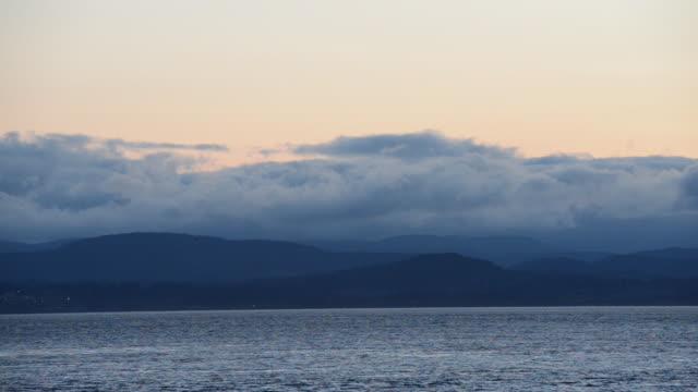 vídeos de stock, filmes e b-roll de time lapse: billowing clouds and dark mountain silhouette rising above the sea - boa postura