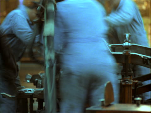 time lapse blue collar workers in car factory assembly line