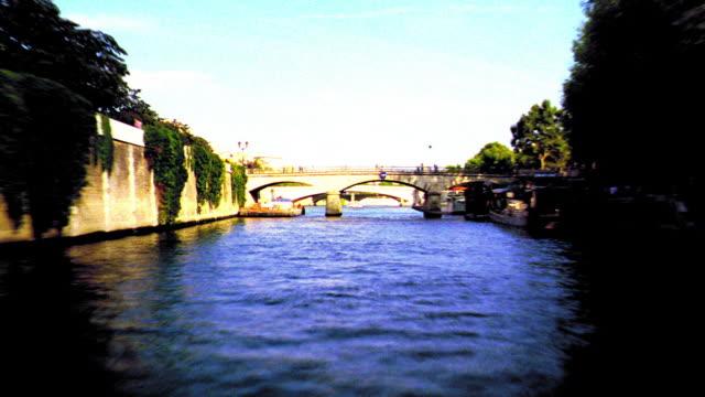 overexposed time lapse boat point of view traveling under all bridges on seine river around ile de la cite / paris - overexposed video stock e b–roll