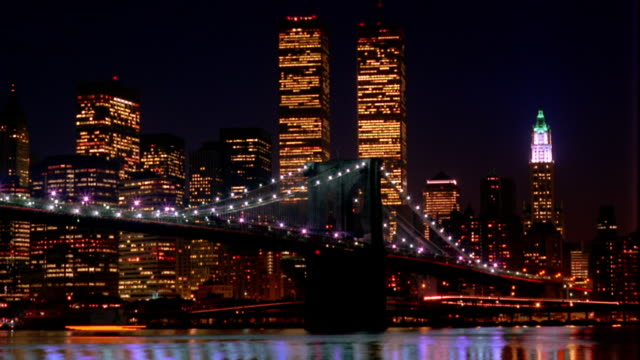 vídeos de stock e filmes b-roll de time lapse boats and traffic on brooklyn bridge with world trade center in background at night / new york city - world trade center manhattan