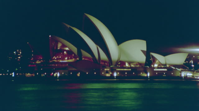 time lapse boats moving in harbor in front of sydney opera house at night / sydney, australia - anno 1999 video stock e b–roll