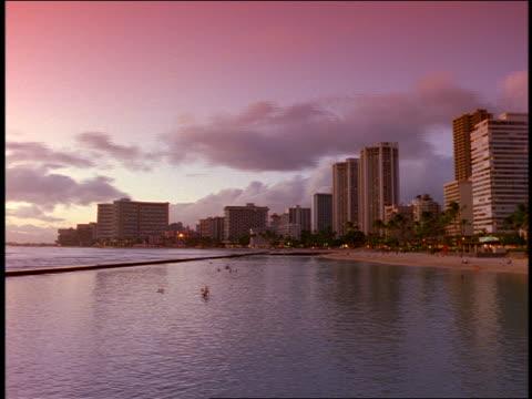 vidéos et rushes de time lapse buildings of waikiki + people swimming in ocean from dusk to night / oahu, hawaii - angle de prise de vue