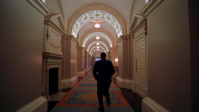rear view time lapse businessman running down state corridor in dublin castle / dublin, ireland - corridoio caratteristica di una costruzione video stock e b–roll