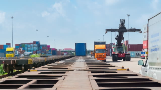 4k time lapse busy traffic in container cargo warehouse at terminal commercial port with mobile crane truck loading container to the freight train, business logistics import export  shipping or freight transportation. - pier stock videos & royalty-free footage