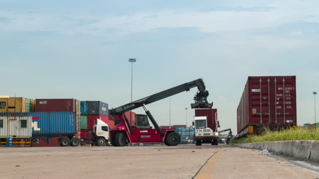 4k time lapse busy traffic in container cargo warehouse at terminal commercial port with mobile crane truck loading container to the freight train, business logistics import export  shipping or freight transportation. - unloading stock videos & royalty-free footage