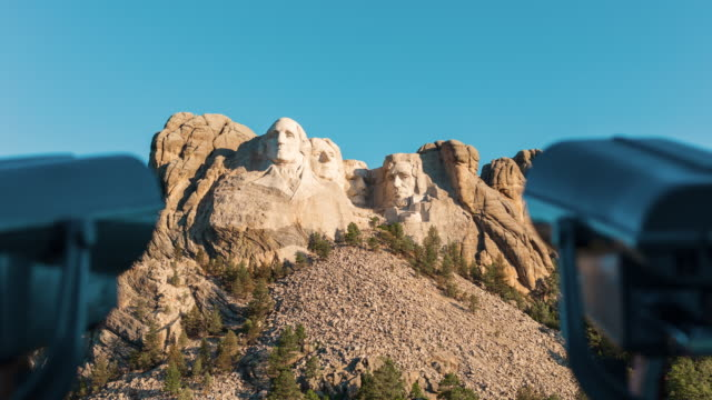 Time lapse camera dollies toward Mount Rushmore National Monument framed with coin operated mechanical binoculars.