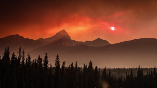 time lapse : canadian wildfire sunset in banff national park, canada - banff national park stock videos & royalty-free footage
