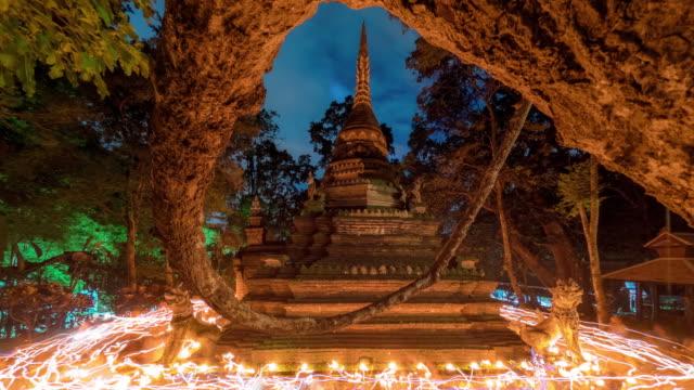 仏教レントデーの夕暮れ時の古代塔周辺のタイムラプスキャンドル行列式 - 四旬節点の映像素材/bロール