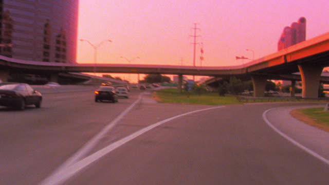time lapse car point of view driving on highway / circling around exits with buildings in background / Dallas, Texas