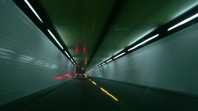 Time lapse car point of view driving through road tunnel following truck / Lyttelton Road Tunnel, New Zealand