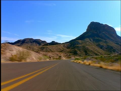 time lapse car point of view on desert road through mountains / big bend, texas - ländliche straße stock-videos und b-roll-filmmaterial