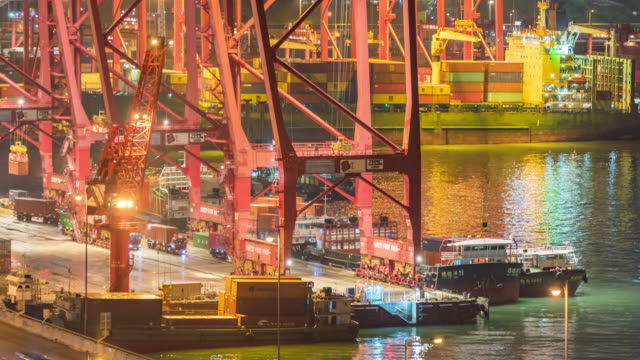 vídeos de stock, filmes e b-roll de transporte do recipiente de carga do lapso de tempo no armazém de distribuição no porto portuário de hong kong com fundo escritório prédio exterior - recipiente