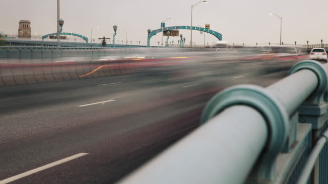 Time lapse, cars and traffic blur down highway across Ben Franklin Bridge.