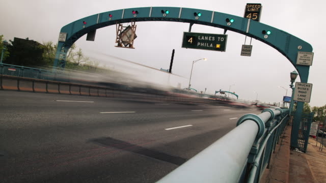 Time lapse, cars and traffic drive on interstate highway across Ben Franklin Bridge.