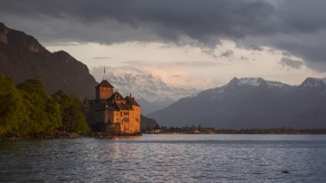 vidéos et rushes de time lapse. chateau de chillon (chillon castle) on the shore of lake geneva with snow covered mountains (dents du midi) in background at dramatic sunset scenery. - montreux