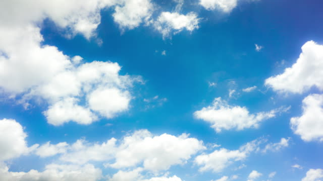 time lapse clip of white fluffy clouds over blue sky - roll over stock videos and b-roll footage