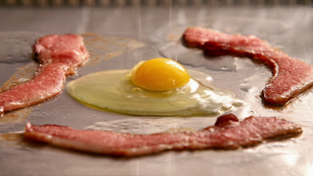 time lapse close up of strips of bacon frying on grill / hand cracking egg onto grill / spatula removing egg and bacon - speck stock-videos und b-roll-filmmaterial