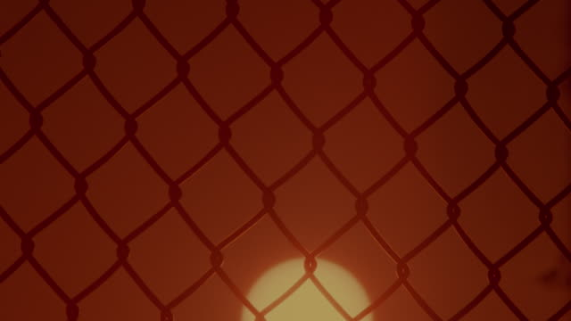 time lapse close up sunrise behind silhouette of chain link fence - beliebiger ort stock-videos und b-roll-filmmaterial