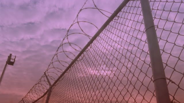 vídeos de stock, filmes e b-roll de time lapse clouds above low angle close up of chain link fence with barbed wire at sunrise - céu romântico