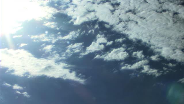 time lapse clouds float through the sky across the sun. - 50 sekunder eller längre bildbanksvideor och videomaterial från bakom kulisserna