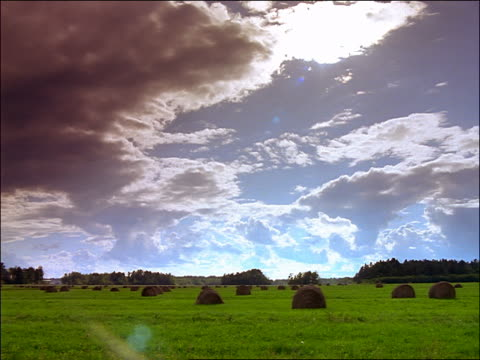 time lapse clouds in blue sky over green field with hay rolls / ontario - ontario canada stock videos & royalty-free footage