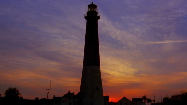 Time lapse clouds moving and sun rising behind silhouetted Tybee Island Light Tower / Savannah, Georgia