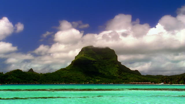 Time lapse clouds moving over rocky green island and ocean / Bora Bora, French Polynesia, South Pacific