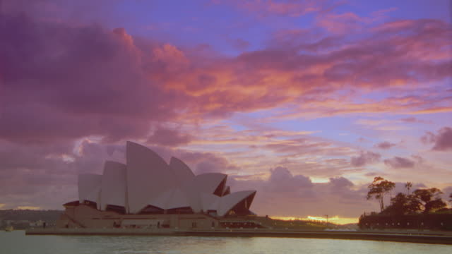 time lapse clouds over boats on harbor + Sydney Opera House at sunrise / Sydney, Australia