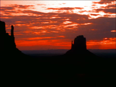 pan time lapse clouds over desert with rock formations / monument valley, utah - romantische stimmung stock-videos und b-roll-filmmaterial