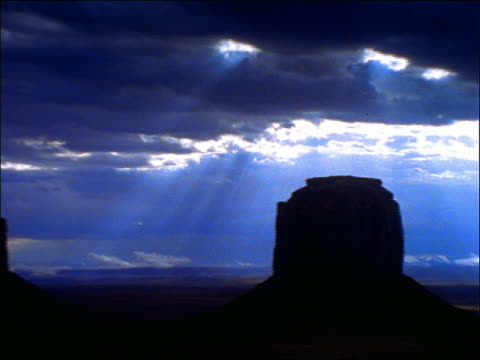 pan time lapse clouds over desert with silhouette of rock formation / monument valley, utah - naturwunder stock-videos und b-roll-filmmaterial
