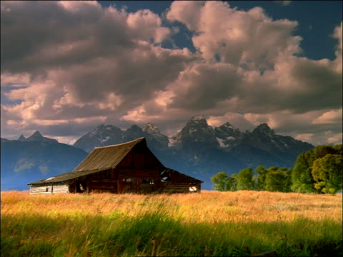 time lapse clouds over grand teton mountains with old barn in foreground / wyoming - parco nazionale del grand teton video stock e b–roll