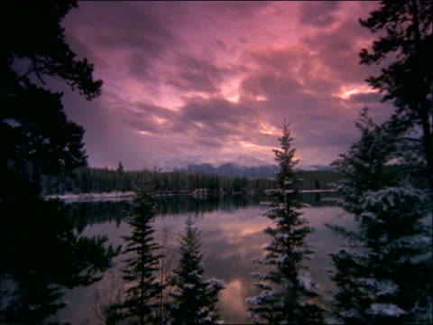 time lapse clouds over lake surrounded by snow covered trees / canadian rockies, banff national park - pinacee video stock e b–roll