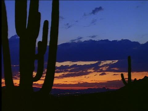 vídeos de stock, filmes e b-roll de time lapse clouds over silhouette of desert at sunset - céu romântico