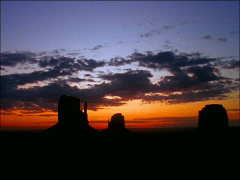 time lapse clouds over silhouette of desert with rock formations / monument valley, utah - romantische stimmung stock-videos und b-roll-filmmaterial
