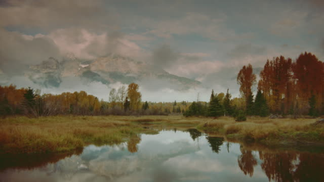 time lapse clouds over snake river and autumn trees / mountains in background / grand teton national park, wyoming - grand teton national park stock videos & royalty-free footage