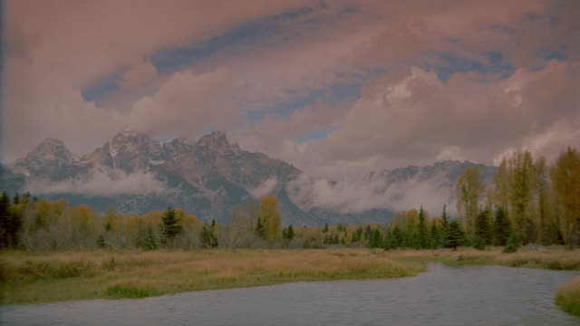 pan of time lapse clouds over snake river and teton mountains in autumn / grand teton national park, wyoming - teton range stock videos & royalty-free footage