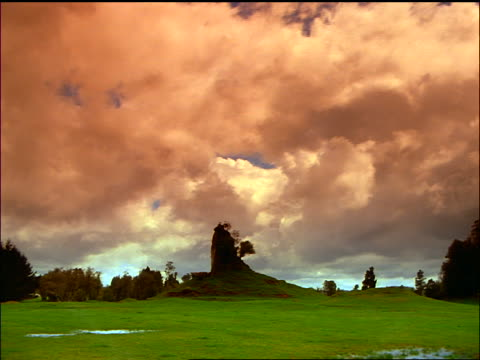 time lapse clouds passing above eroded volcanic hill with tree / north island, rotorua / new zealand - north island new zealand stock videos & royalty-free footage