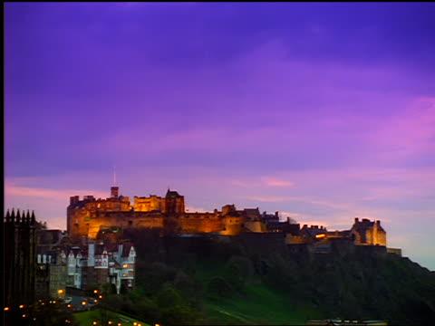 time lapse clouds passing above lighted edinburgh castle estate at dusk / edinburgh, scotland - edinburgh castle stock videos & royalty-free footage