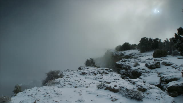 time lapse clouds passing over canyon during snowstorm in desert / grand canyon national park, arizona - grand canyon national park stock videos & royalty-free footage
