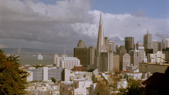 vidéos et rushes de time lapse clouds passing over san francisco skyline / oakland bay bridge in background - transamerica pyramid san francisco