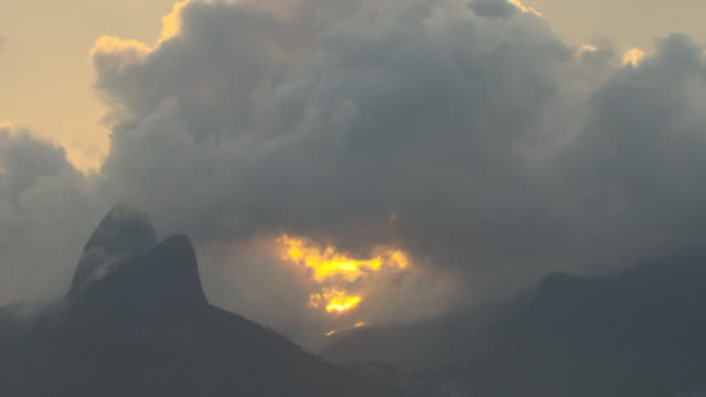 time lapse clouds passing over two brothers mountain peaks, yellow sunset shining through /wide shot time lapse low clouds passing over buildings and... - dramatic landscape stock videos & royalty-free footage