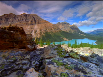 time lapse clouds + point of view over rocks towards mountain lake, forest + canadian rockies / banff national park - banff nationalpark stock-videos und b-roll-filmmaterial
