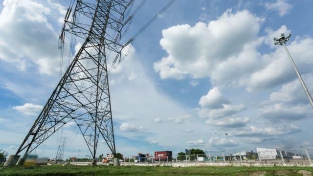 vídeos y material grabado en eventos de stock de lapso de tiempo, nublado moviéndose en el cielo, torre de potencia de alto voltaje, estructura de polo eléctrico con tráfico. - cuadrícula