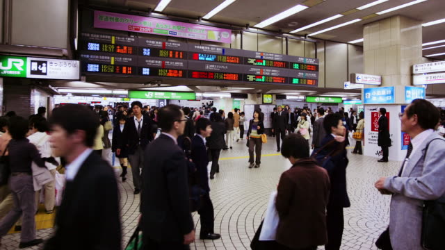 time lapse commuters passing under arrivals board in shinjuku jr station / tokyo, japan - rail transportation stock videos & royalty-free footage