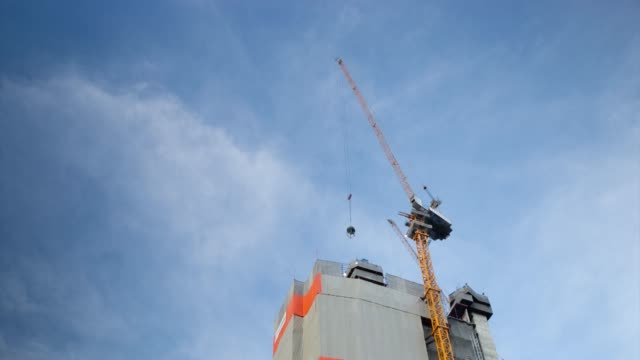 time lapse construction building with cranes and clouds on  blue sky. - high up stock videos & royalty-free footage