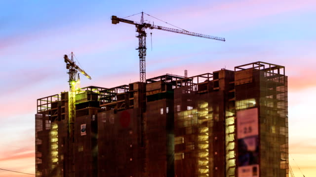 hd time lapse, construction building with working crane at dusk - figurine stock videos & royalty-free footage