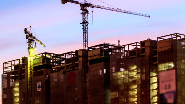 hd time lapse, construction building with working crane at dusk - figurine stock videos and b-roll footage