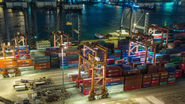 4k time lapse : container cargo warehouse at terminal commercial port and working crane bridge load container to small ship at night for business logistics, import export, shipping or transportation. - freight elevator stock videos & royalty-free footage