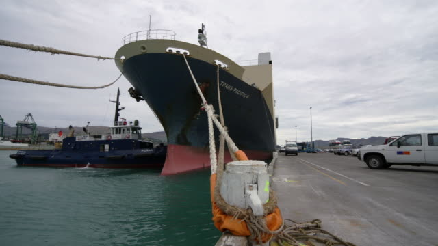 Time lapse container ship moored to dock / workers releasing mooring line and tugboat pulling ship away / Port of Lyttelton, New Zealand