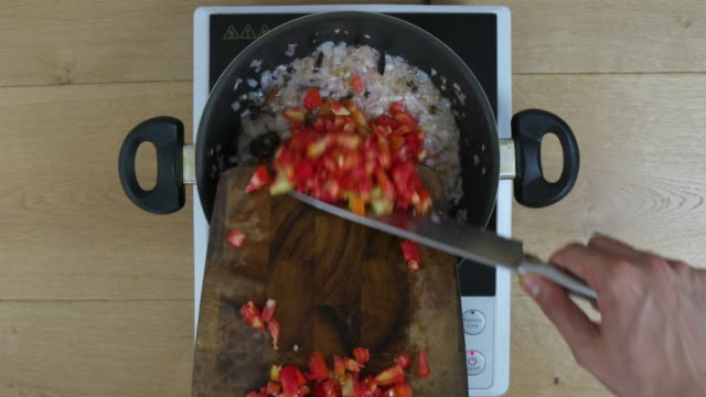 Time Lapse, cook adds finely chopped tomatoes and stirs to mix a base of onions, ginger, garlic and various Indian spices, masalas, herbs, etc to create an authentic Indian curry base